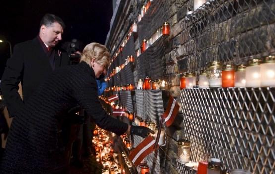 Lāčplēša dienas vakarā tūkstošiem cilvēku noliek svecītes pie Rīgas pils mūra